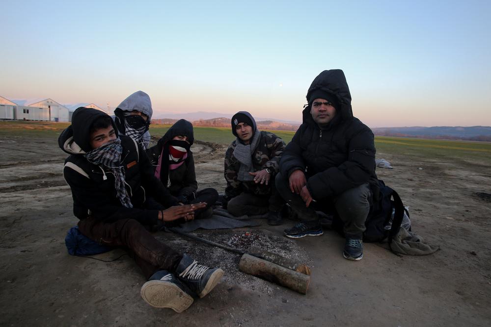 Un groupe de jeunes migrants iraniens bloqués à la frontière greco-macédonienne depuis trois jours tente de se réchauffer autour d'un petit feu. Depuis que seuls les Syriens, les Afghans et les Irakiens sont autorisés à passer, les ressortissants des autres pays trouvent d'autres moyens, clandestins.