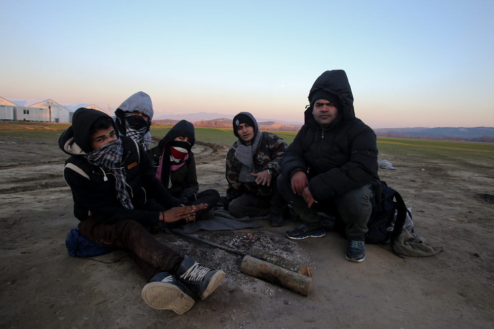 A group of young Iranian migrants who have been stranded at Greece's border with Macedonia for three days, try to keep warm around a small fire (Dimitris Tosidis/IRIN)