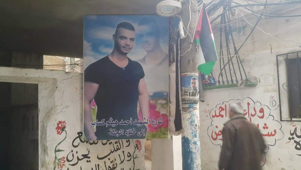 A poster of a young camp resident who died while trying to fix electricity cables