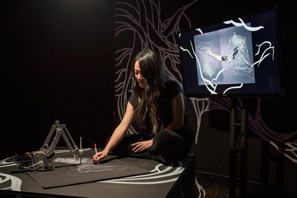 Artist Sougwen Chung (alum, 2014-2015) demos drawing robot D.O.U.G., in a collaboration with Yotam Mann (alum, 2014-2015)