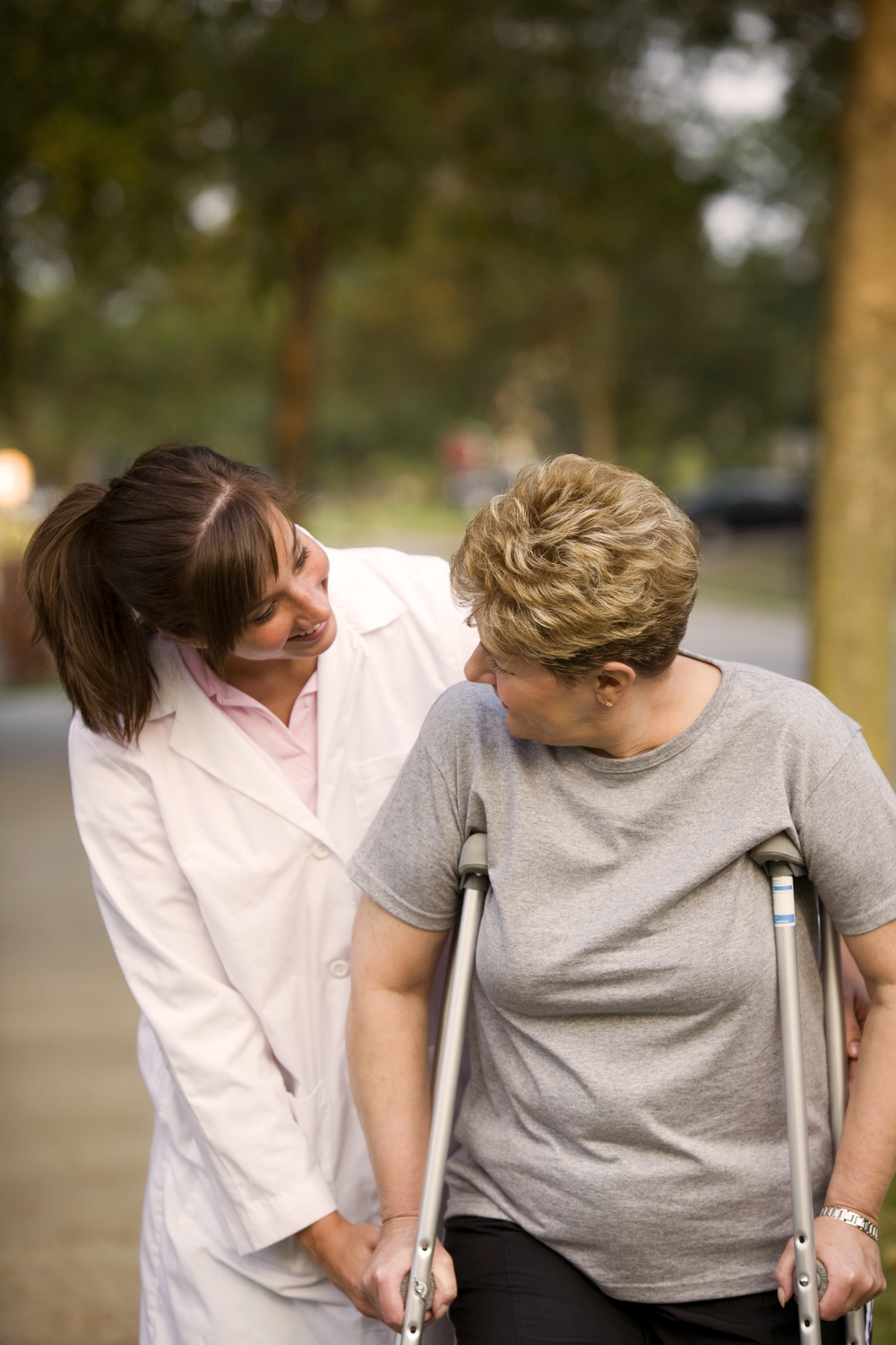 Nurse helping woman with crutches