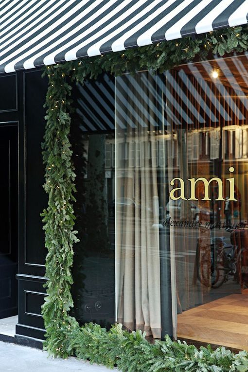 Ami Storefront; Garland Wreath and lights surround the entire glass storefront window. Elegant and Timeless