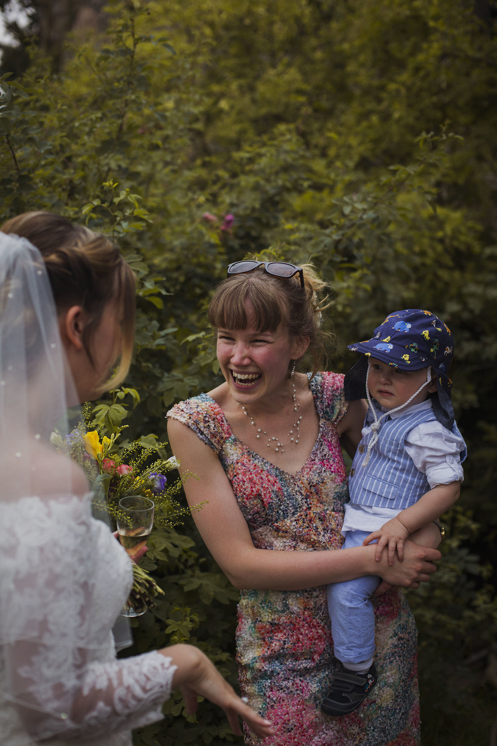 mother holding baby boy smiling with the bride at wedding at usk castle