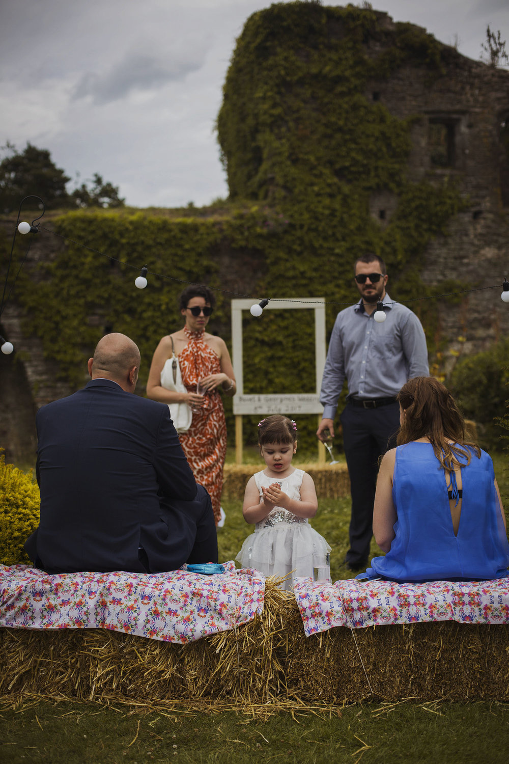 wedding guests sitting on hay bales at usk castle