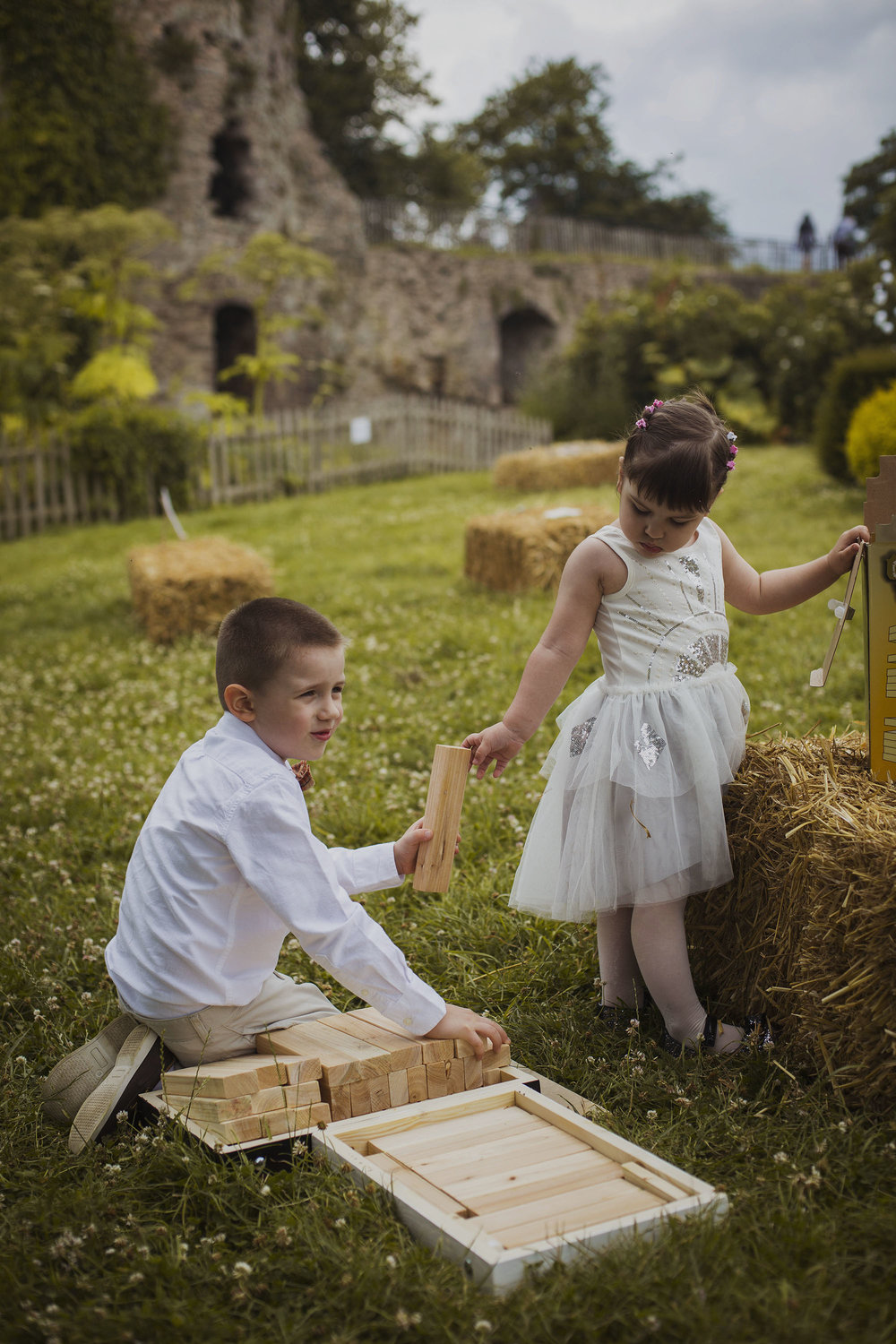 little girl handing giant jenga block to her older brother at wedding at usk castle