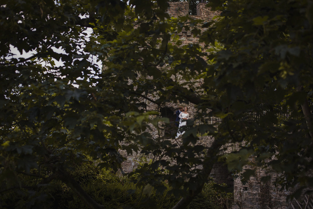 bride and groom at usk castle pictured through trees
