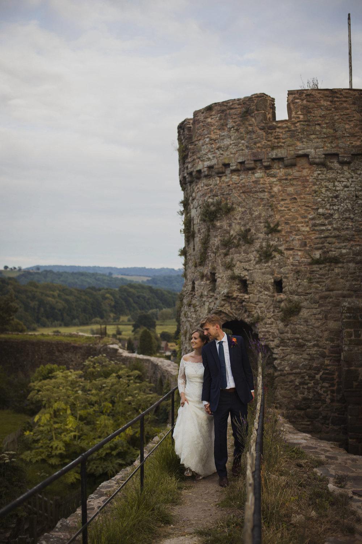 bride and groom portrait walking together at usk castle