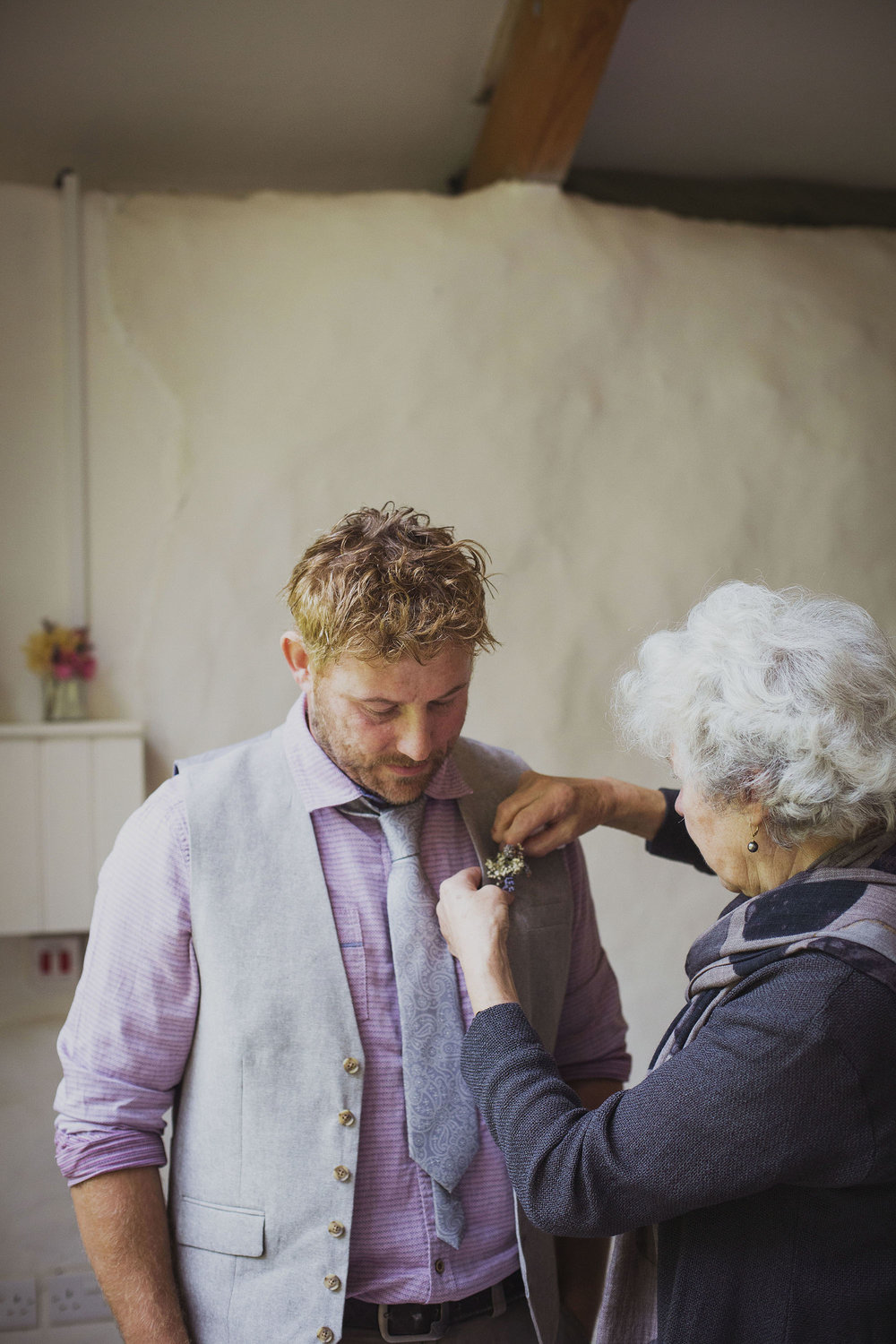groom and groom's mother attaching button hole at nantwen wedding venue