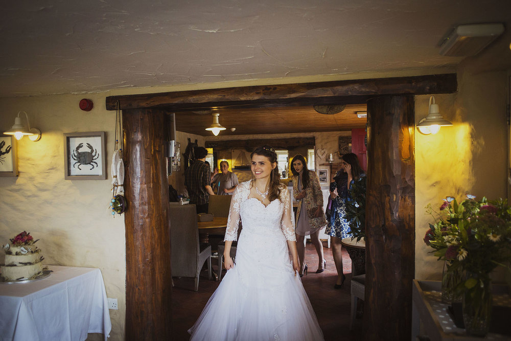 bride entering wedding dinner at the old sailors dinas cross newport pembrokeshire