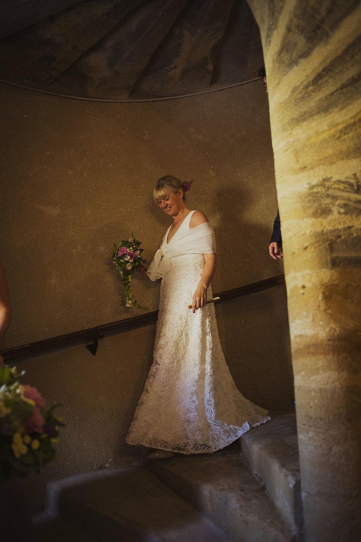 bride walking downstairs at bridal preparations at chateaux des ducs de joyeuses france destination wedding photography