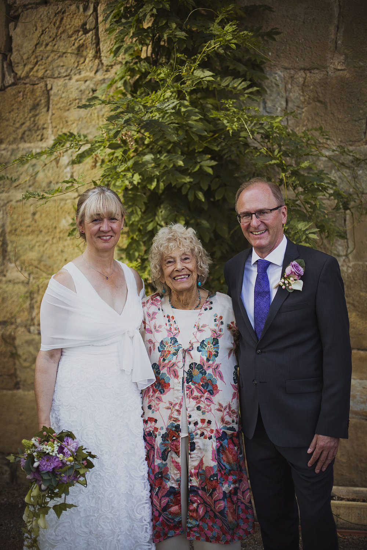 bride and groom with family friend at chateaux des ducs de joyeuses france destination wedding photography