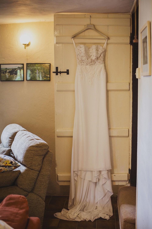 bride's dress hanging in cottage somerset wedding