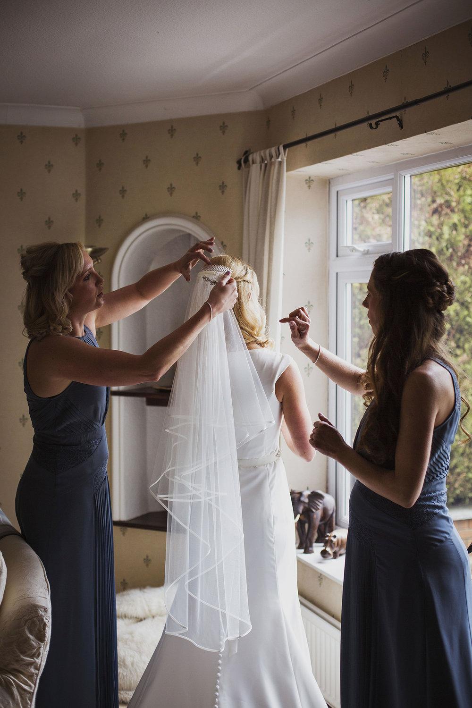 bride putting on veil at diy wedding in midlands