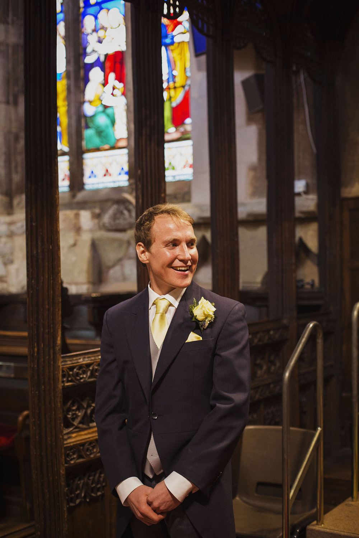groom's reaction at guests arriving at knowle parish church diy wedding