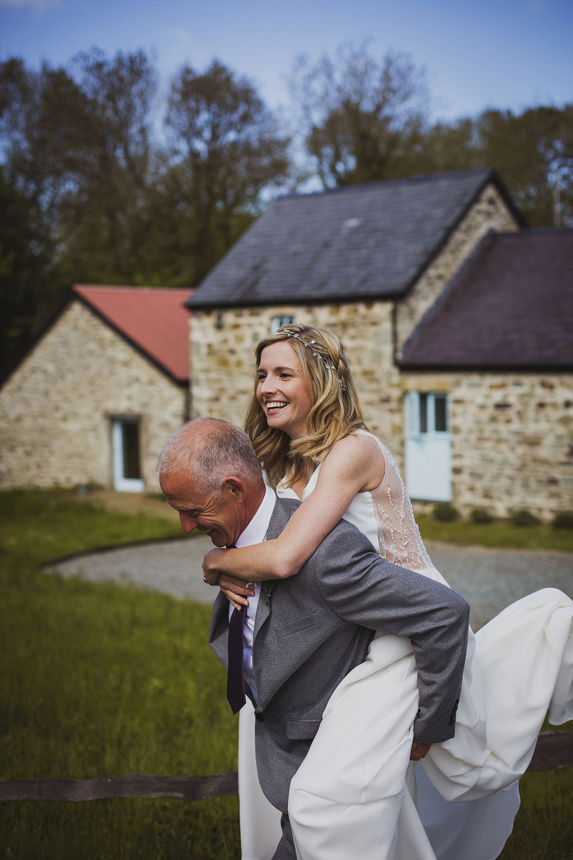 father carrying bride at nantwen wedding
