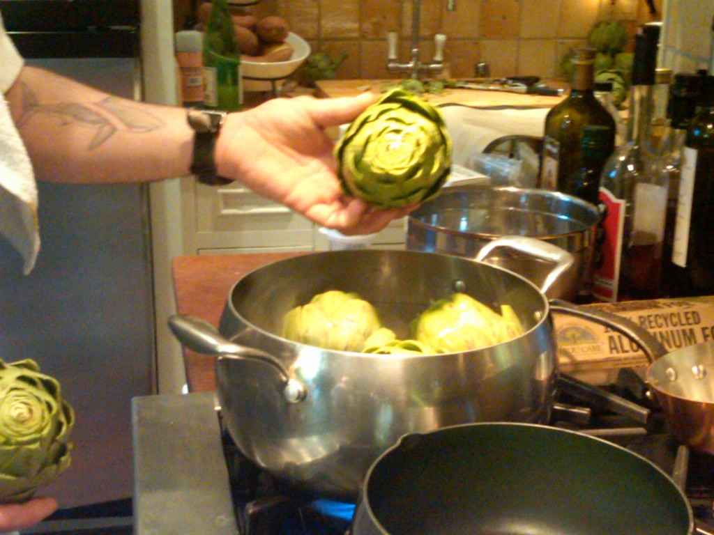 PLACE THE ARTICHOKES IN SALTED ACIDULATED SIMMERING WATER. Acidulated water is water where some sort of acid is added—often lemon juice, lime juice, or vinegar—to prevent cut or skinned fruits or vegetables from browning so as to maintain their appearance.