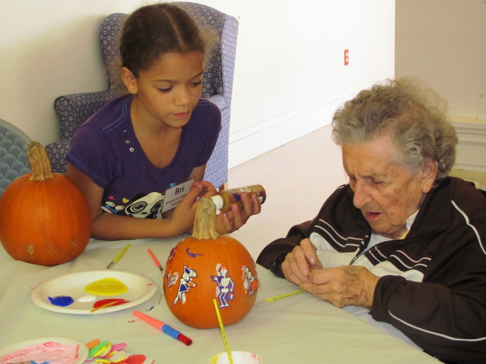 Kay_Christopher_and_child_decorating_pumpkin.jpg