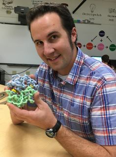 Jim Lane, holding a model of the human CFTR protein that is responsible for causing cystic fibrosis.