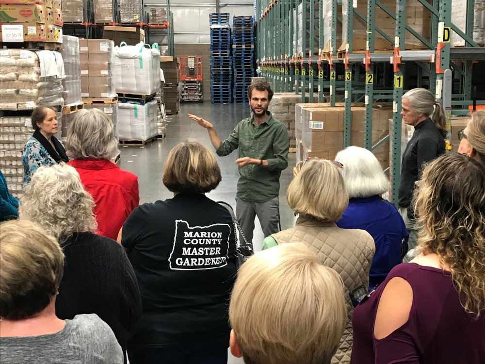 Devin Dinihanian, OFB Garden Educator Coordinator, gives OMGA representatives a tour of the expansive warehouse.
