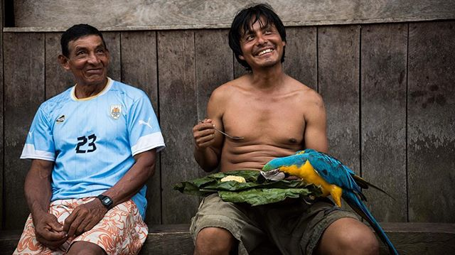 Julio, from Atalaya, the only port town inside Manu National Park, ate and fed his traditional pet macaw during his work break while chatting about soccer with his friend, Mateo. Even when they wore modern clothes and accessories, like Mateo's casio watch, they have never left Atalaya and considered themselves men from the jungle. 📷: @lina_collado