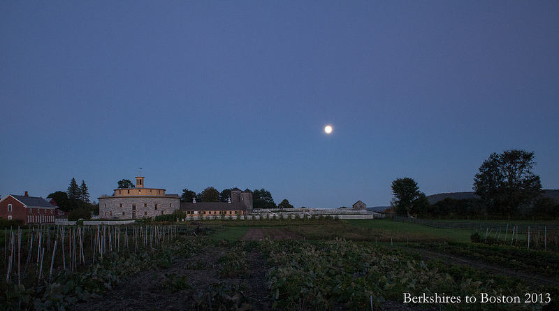 The moon rises over Hancock Shaker Village as riders gather for the tour