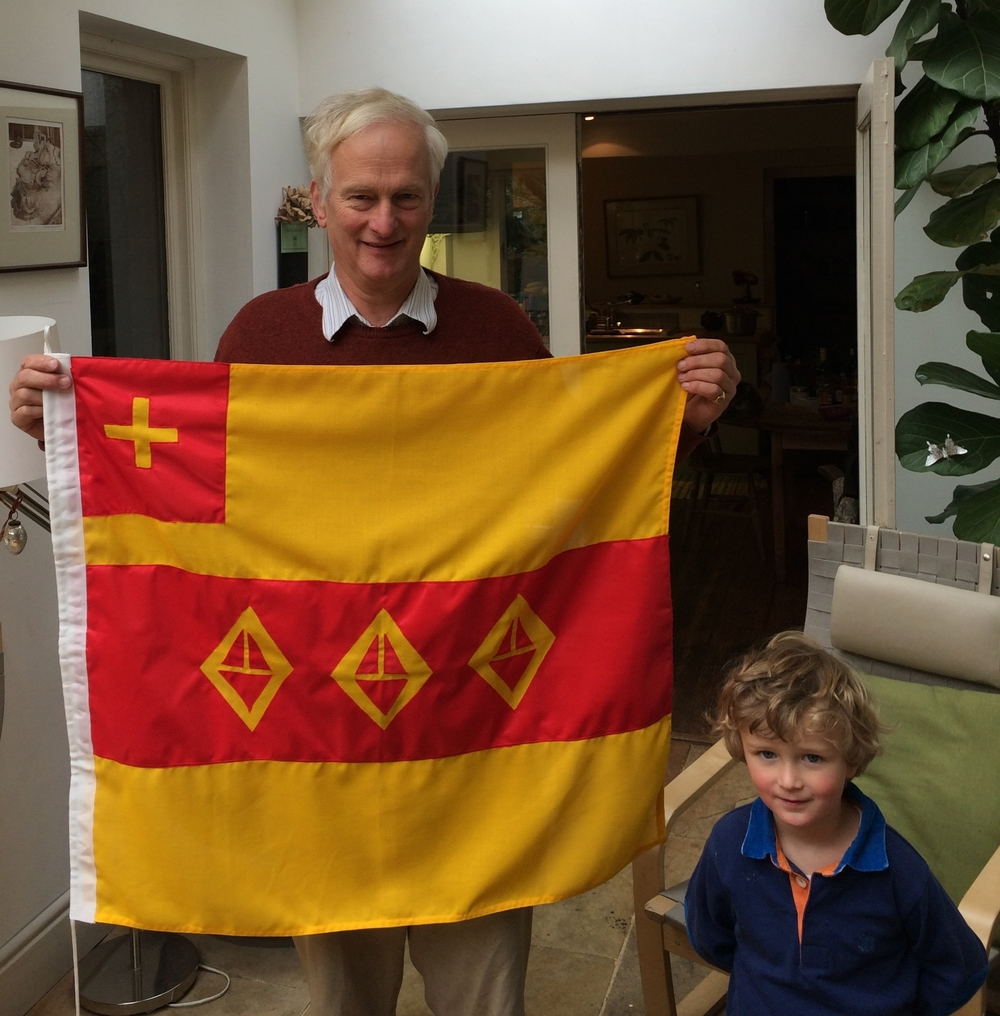 Jonathan Shackleton with a reproduction of the Shackleton family flag brought to the Antarctic and his grandson, Henry Shackleton.