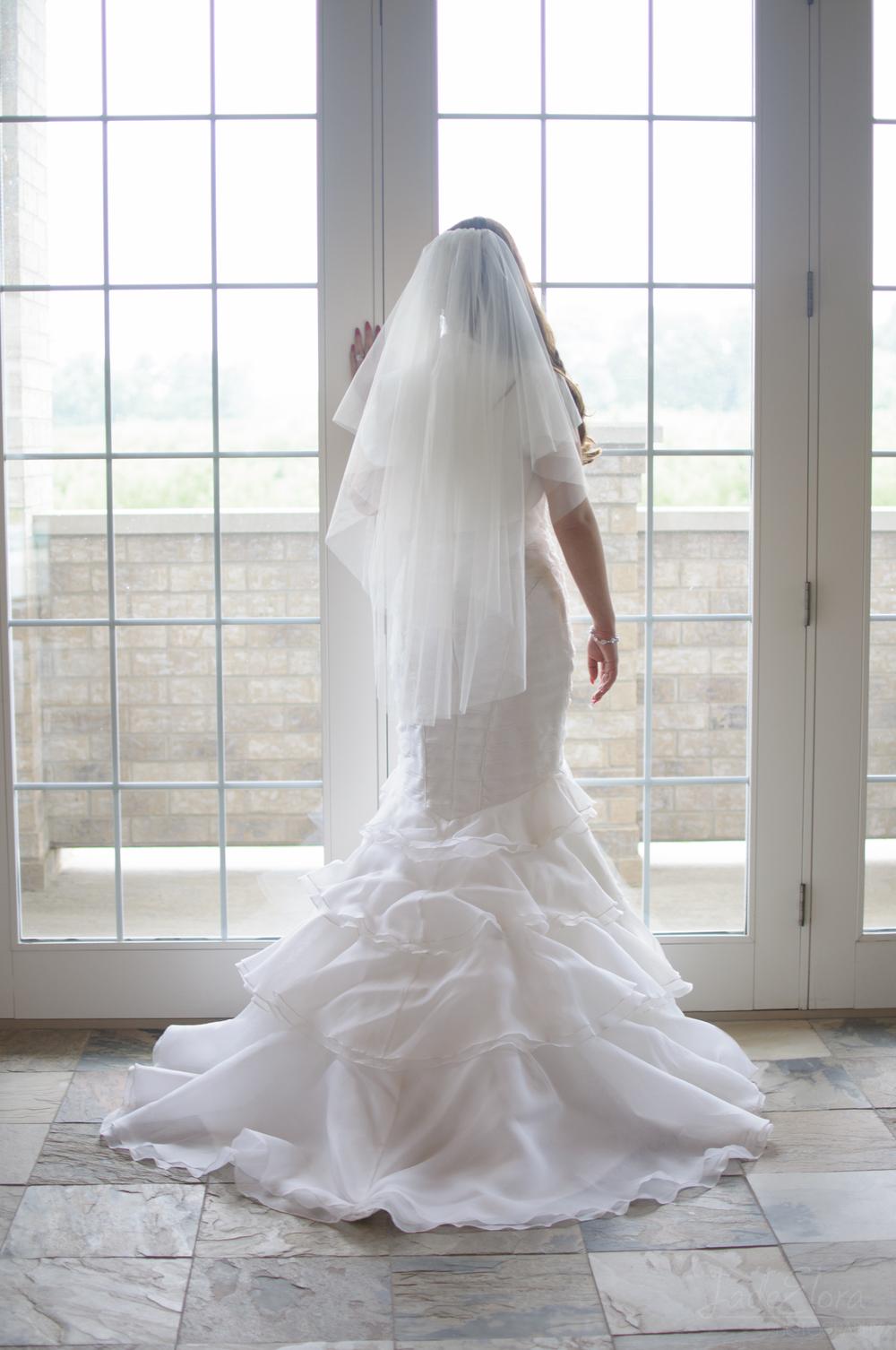 Bride in Mermaid Dress Looking Out Window