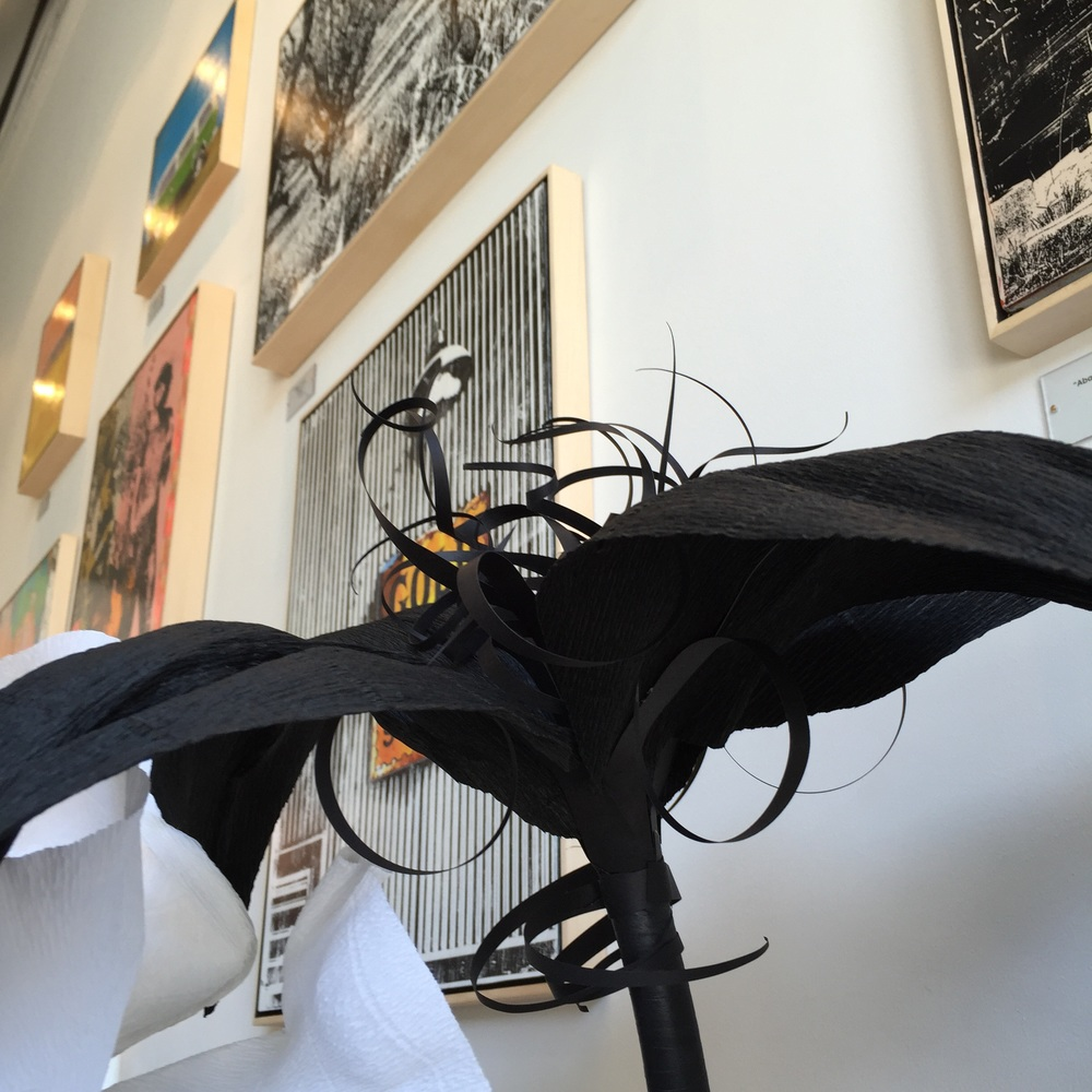 Detail of black lily in front of Deanna Feinelli's artwork.