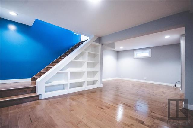 Downstairs rec room with built in shelving and under stair storage