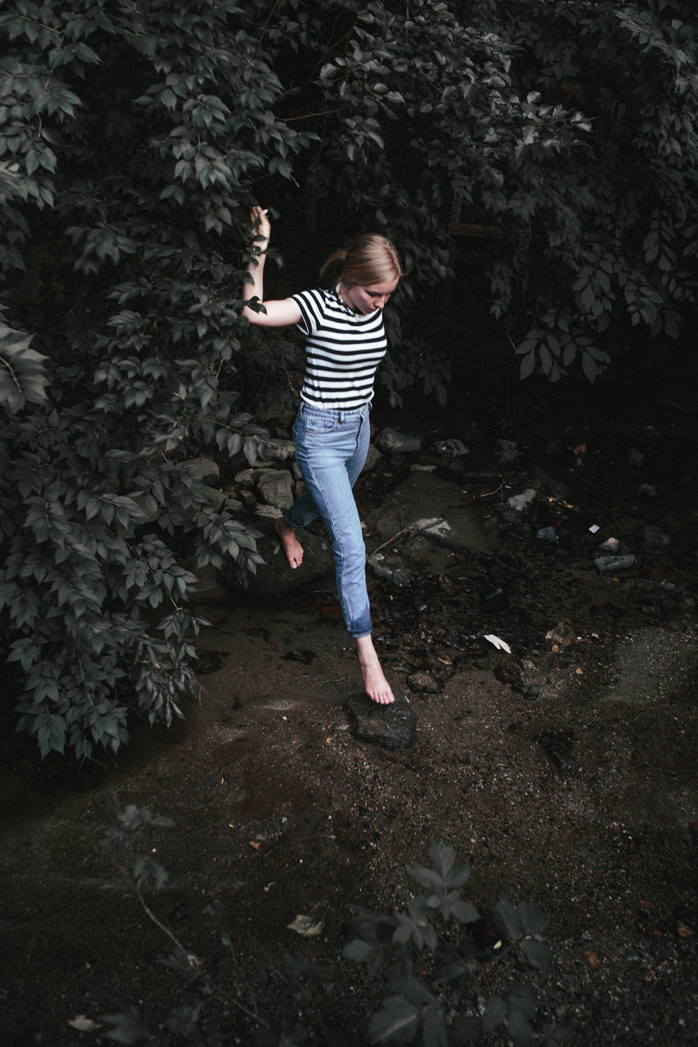 Portrait of woman jumping into a stream