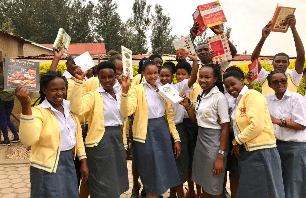 Esther's Aid Culinary Arts students pose for a photo with their new cookbooks