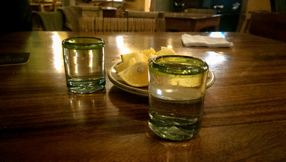 two shots of mezcal with orange slices