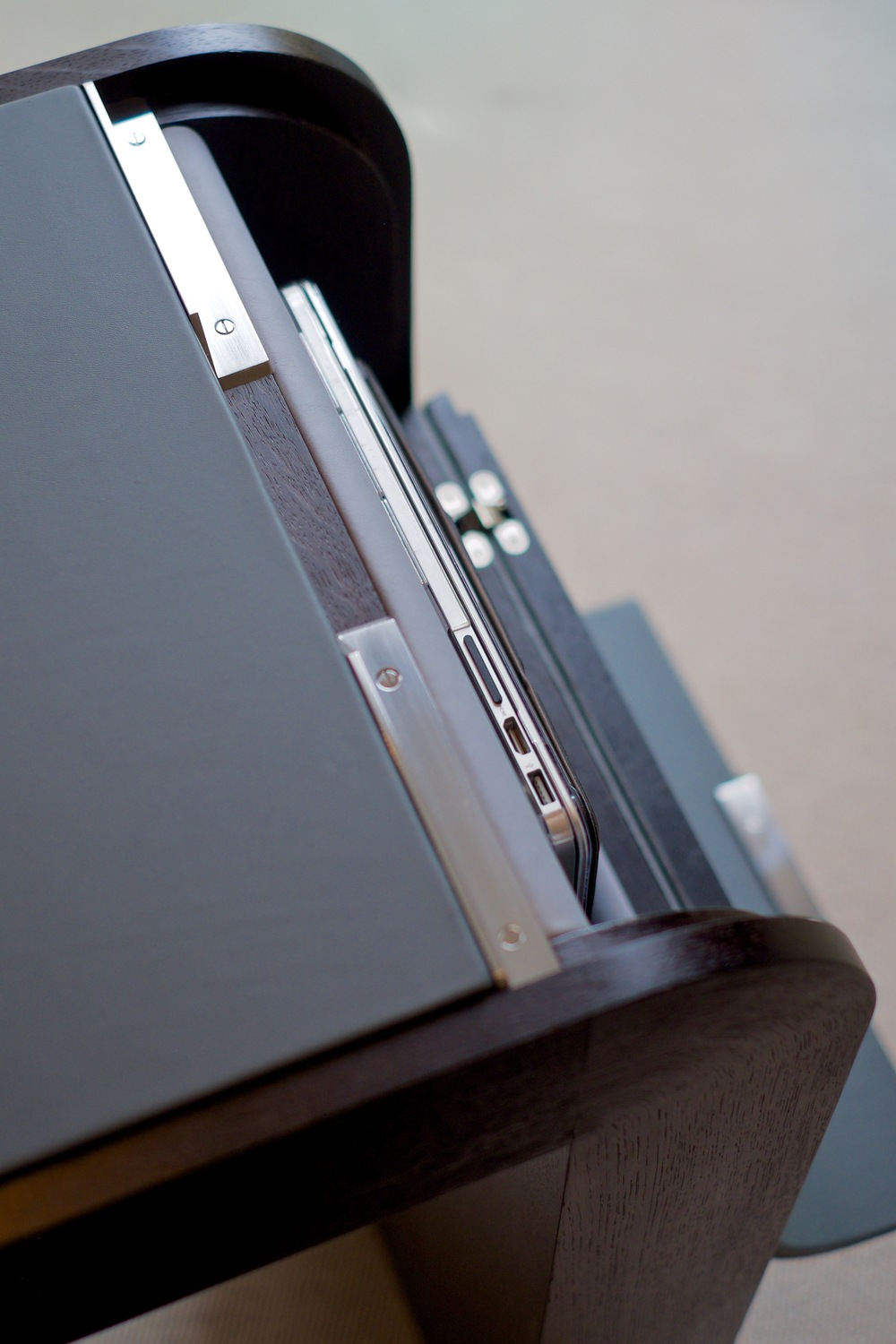 Macbook and iPad in the leather lined storage compartment. The door is left open, but can be shut completely, in-keeping with the desk clean lines