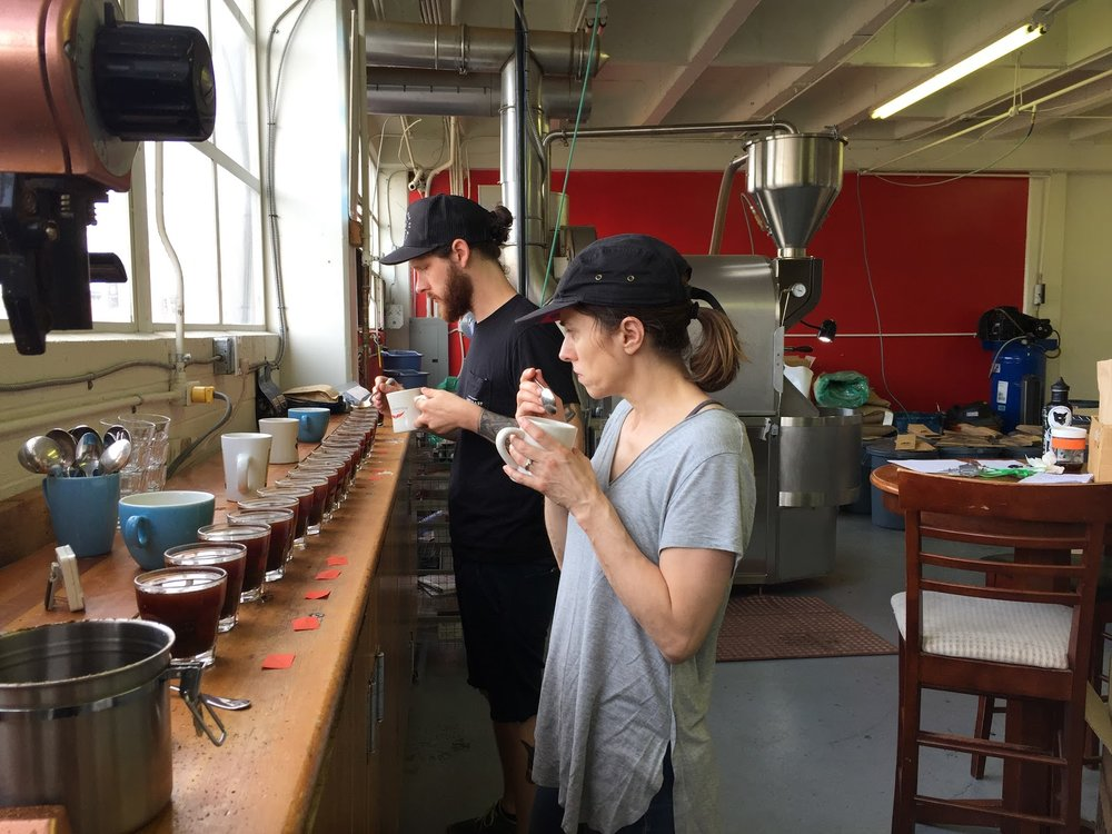 Staff Joel Harrison and Christine Esparolini cupping production (Photo courtesy of Kuma Coffee)