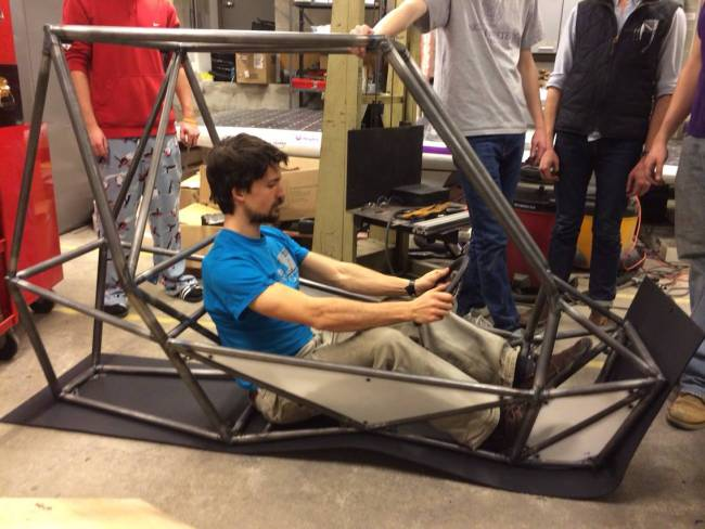 Mike Jastram trying out the (eventual location of the) driver's seat and holding onto a very maneuverable wheel.