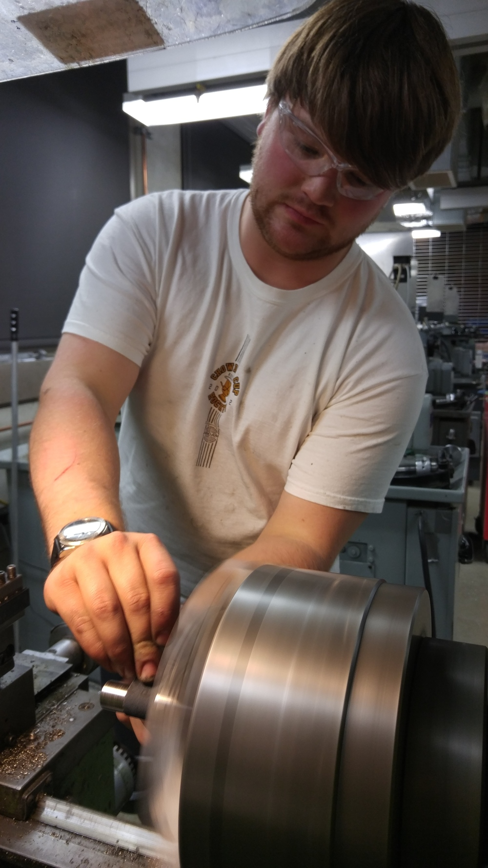 Luke fine-tuning a part on the lathe