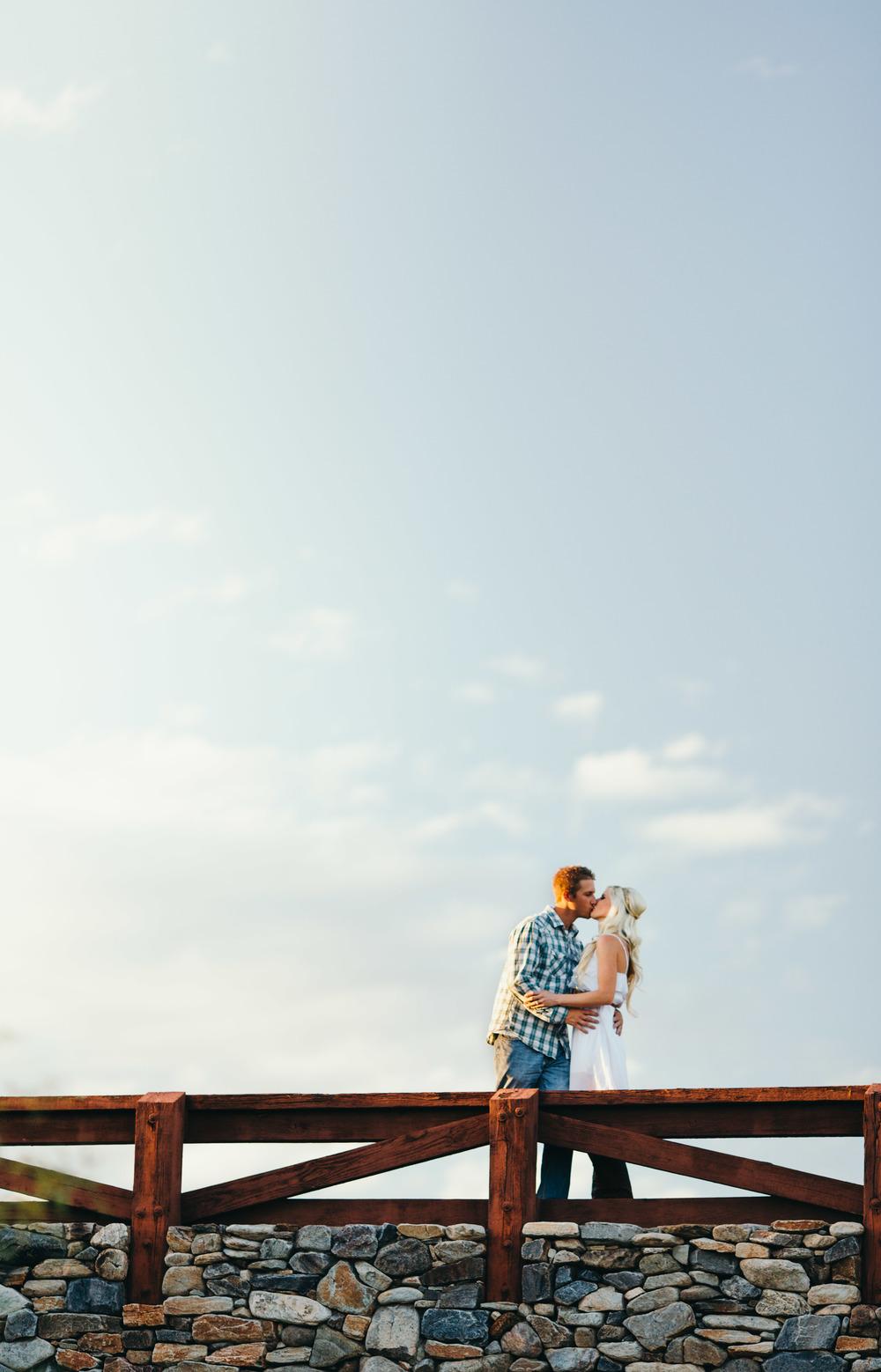 Engagement Couple Kissing on Bridge