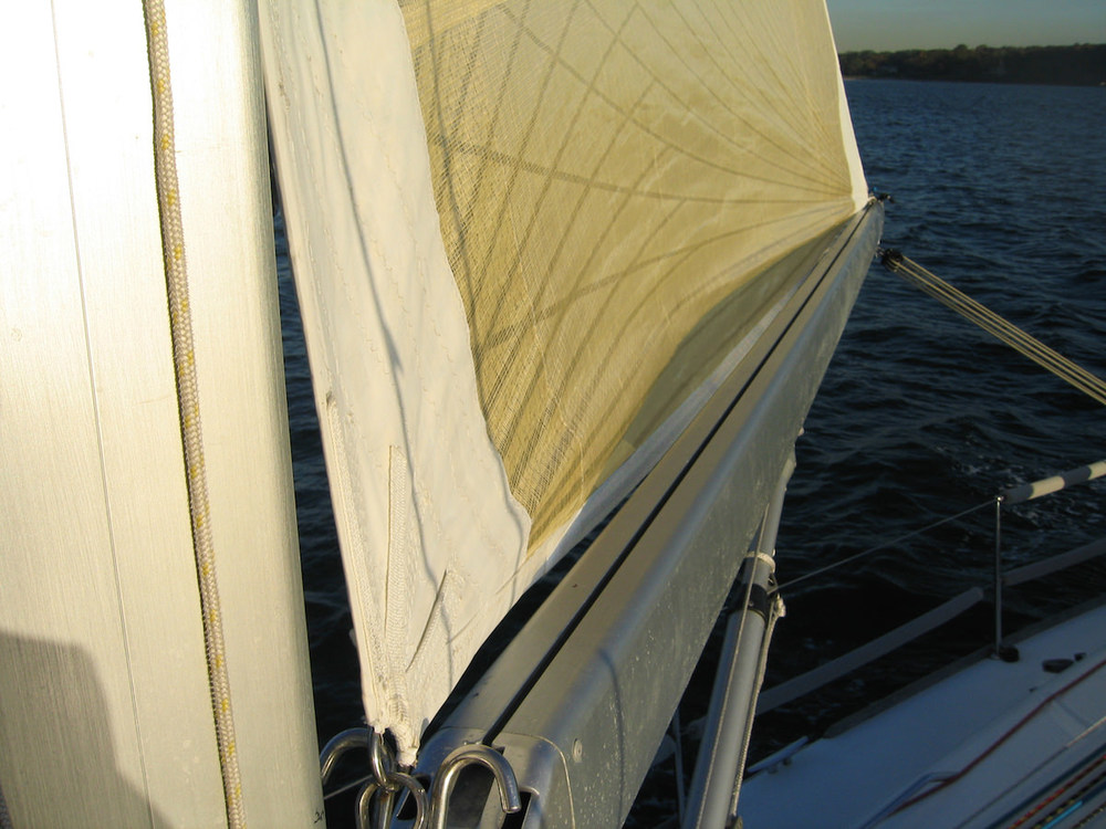 Not attaching the foot of the sail to the boom provides a much better aerodynamic shape without reducing strength.