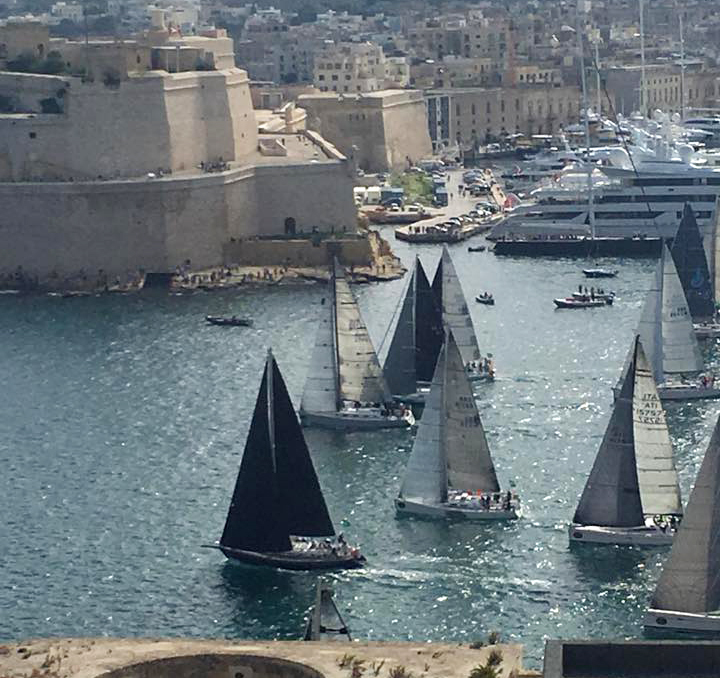Libby O'Brien's photo showing TRIPLE LINDY (black sails and fixed sprit) winning the start of IRC Class 5 of the 2017 Rolex Middle Sea Race.