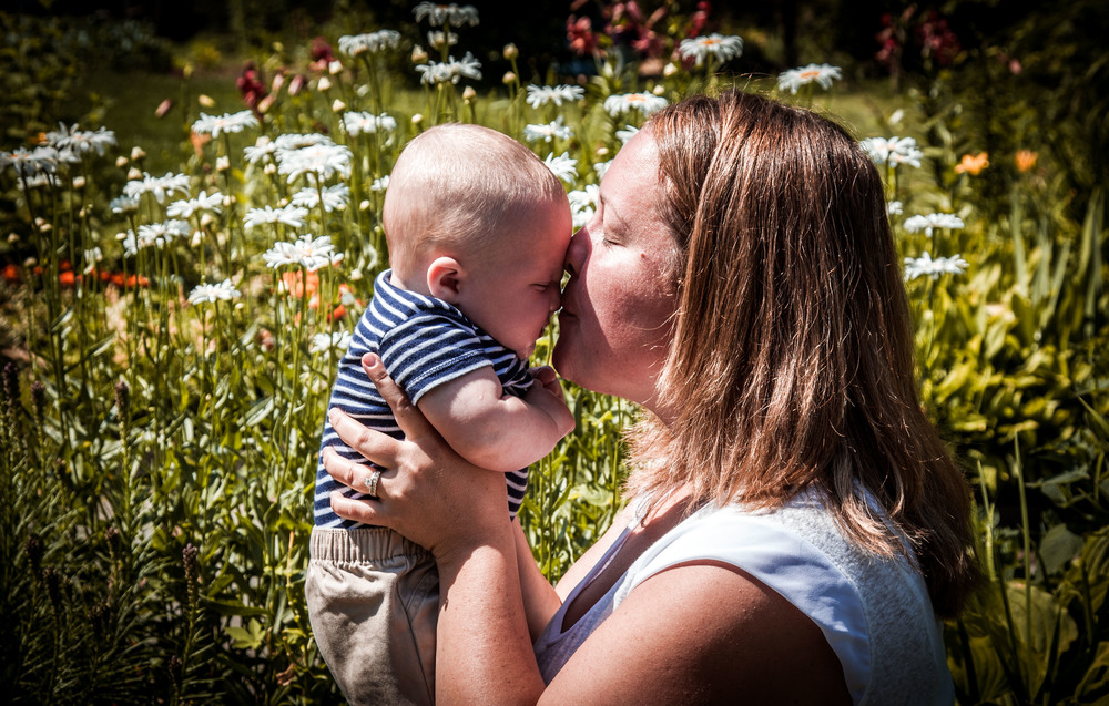 mother kissing baby in flowers