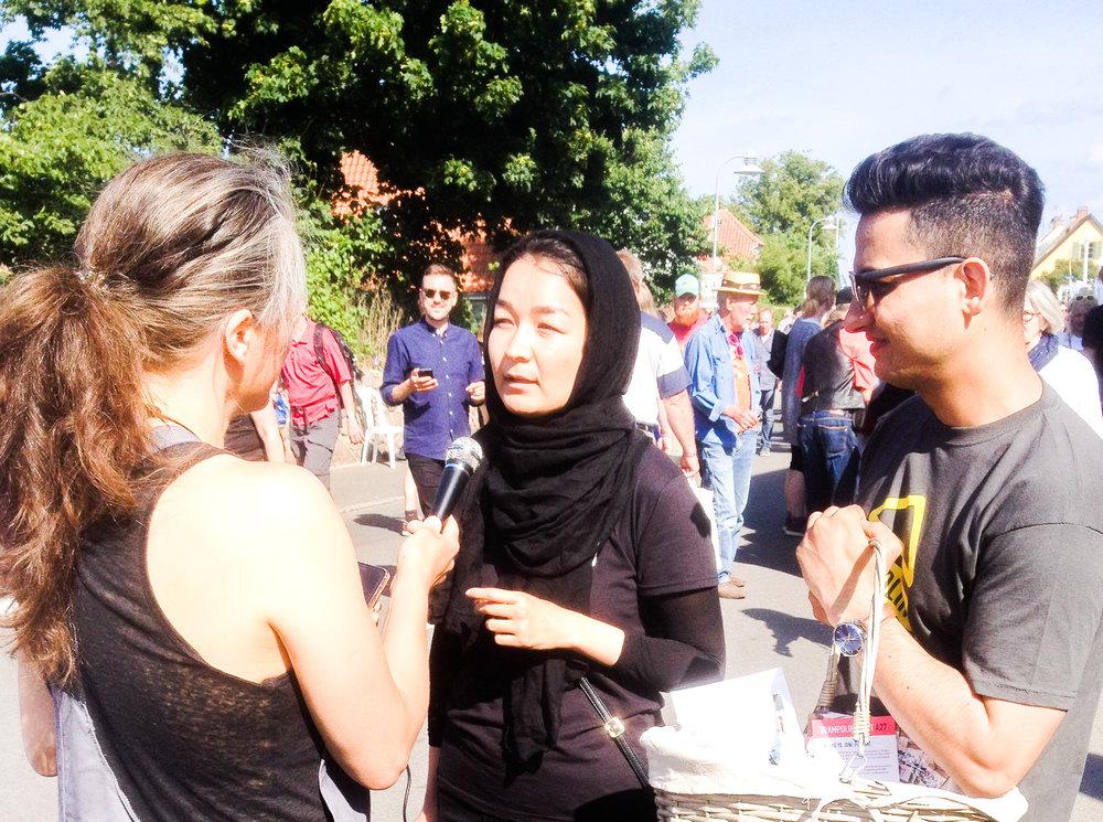 Masoumeh (midten) and Hedayat (højre) fortalte mange mennesker om Trampolinhuset til Folkemødet i juni 2018. Foto: Julie Raun.