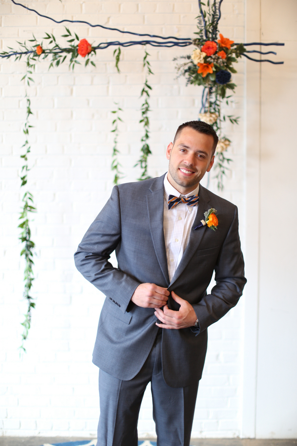 Groom in a grey suit with orange and blue bowtie