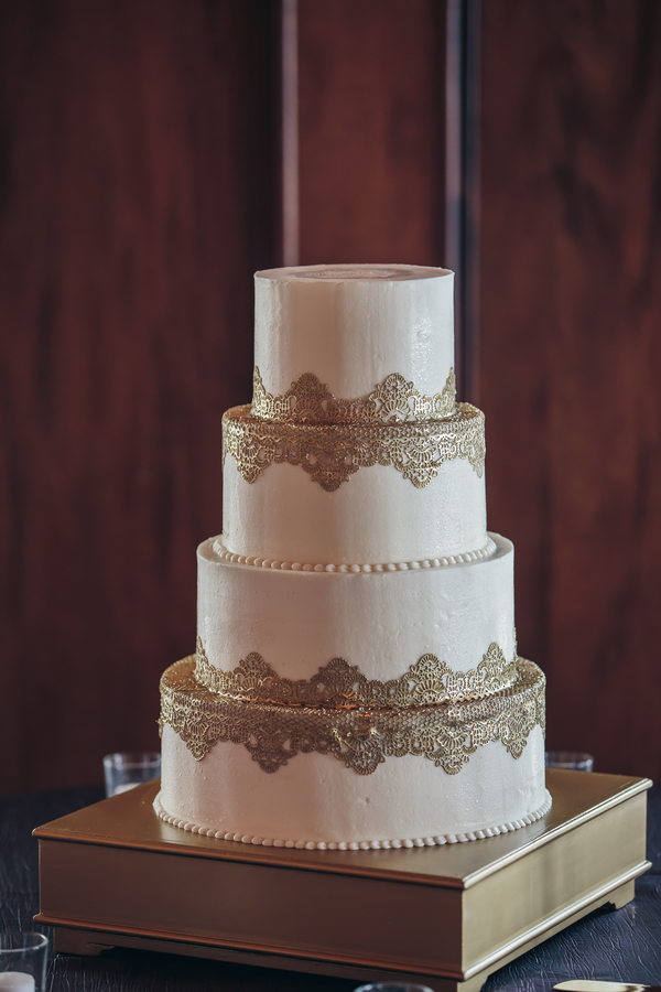 Elegant four-tiered cake with gold detailing by Delicious Desserts at Harborside East wedding