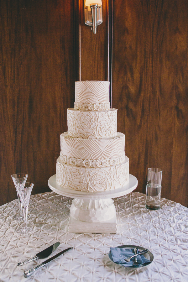 Four-tiered cake by Wedding Cakes by Jim Smeal at Collins + Kinsey's Harborside East wedding photographed by Hyer Images