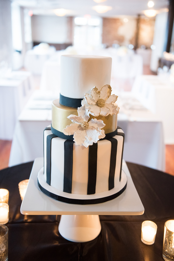 Three tiered glam gold, white and black cake by DeClare Cakes at Rice Mill Building wedding.