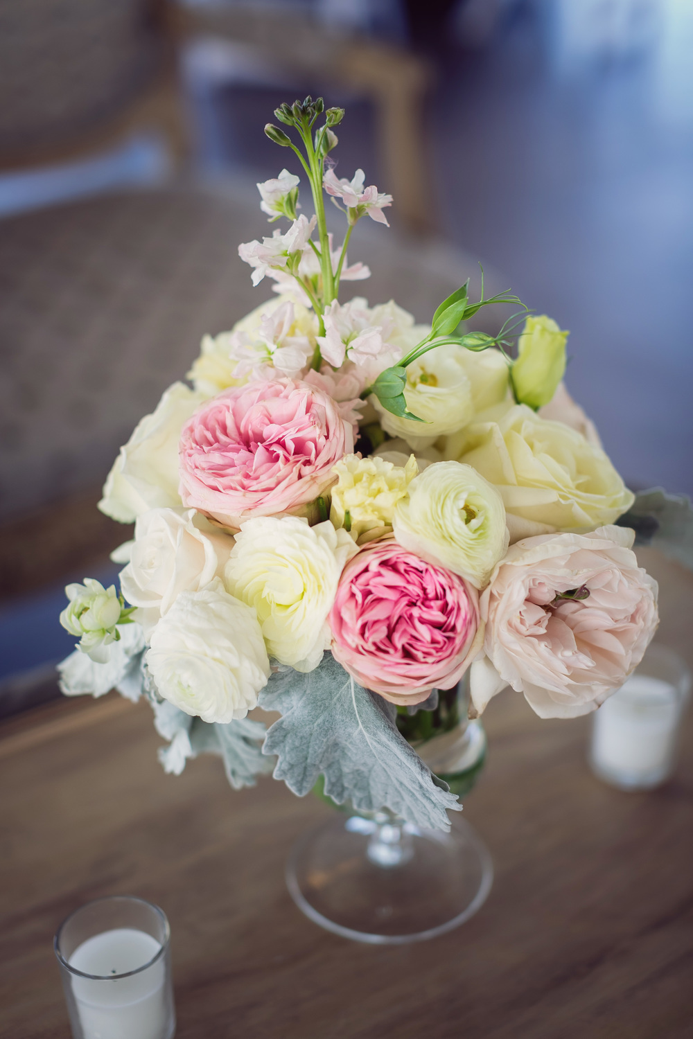 Pink garden roses, white ranunculus and dusty miller centerpieces from Charleston florist Engaging Events