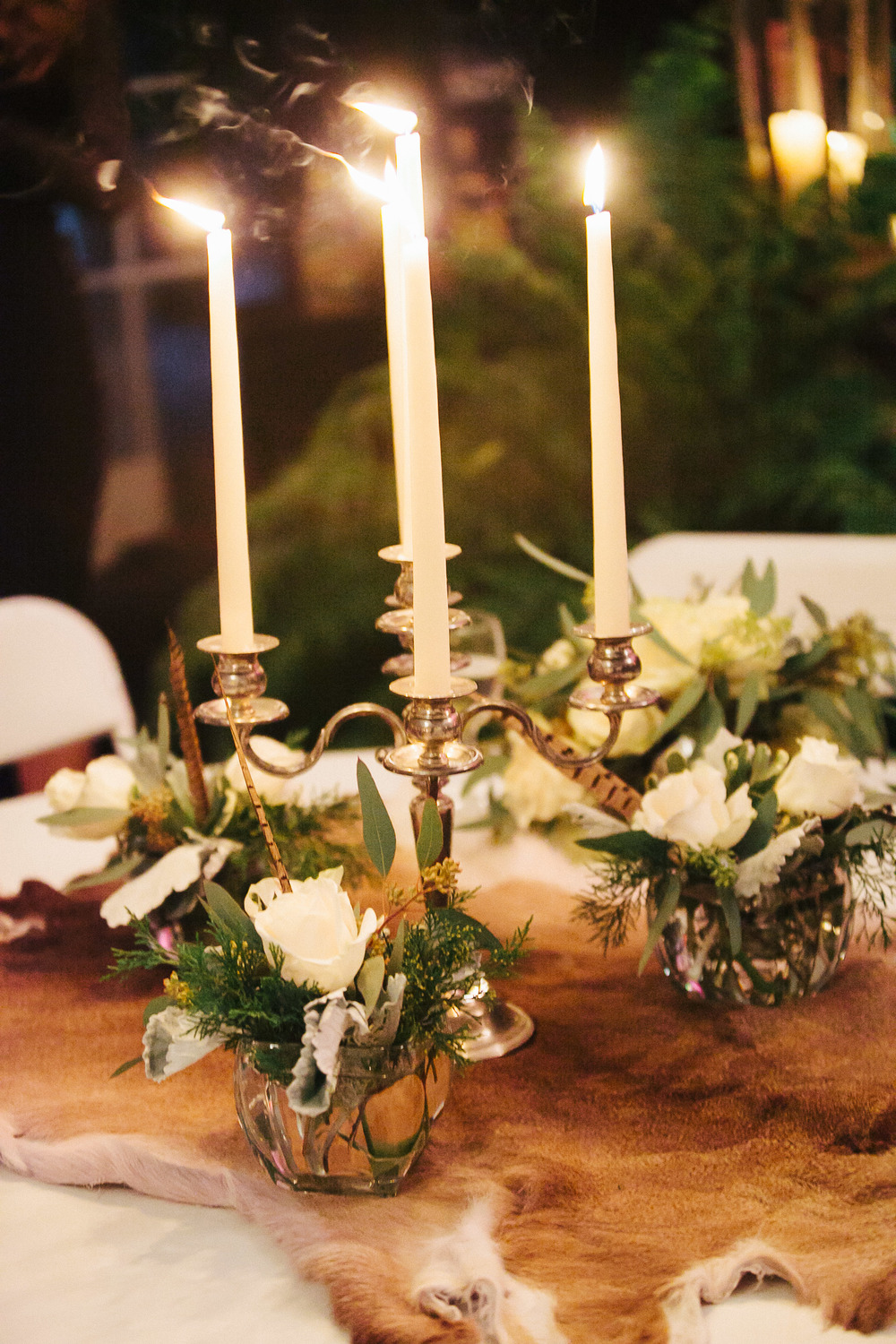 Lush centerpieces of white roses, hydrangeas, spanish moss and pheasant feathers, animal fur table runners and antique candelabras
