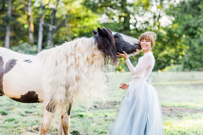 Bride a grey tulle wedding skirt with her horse at rustic farm elopement