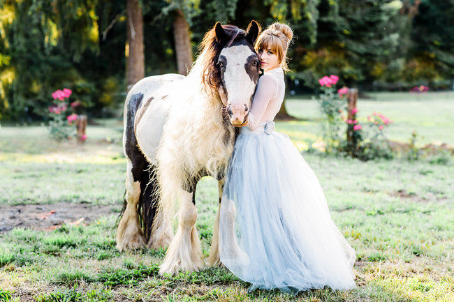 Bride in a grey tulle wedding skirt on a farm with a horse