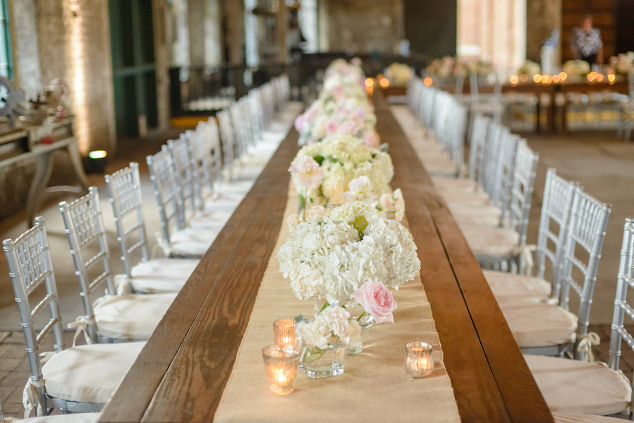 Rustic wedding decor with burlap table runners and white hydrangea centerpieces with pink garden roses and silver chivari chairs